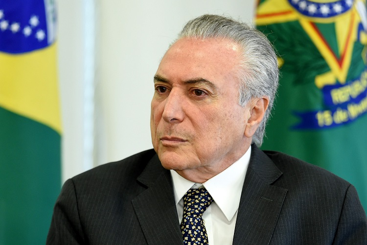 Brazilian President Michel Temer gestures during a meeting with  businessmen at Planalto Palace in Brasilia, on May 25, 2017. Brazilian soldiers deployed Wednesday to defend government buildings in the capital Brasilia after protesters demanding the exit of President Michel Temer smashed their way into ministries and fought with riot police. / AFP / EVARISTO SA