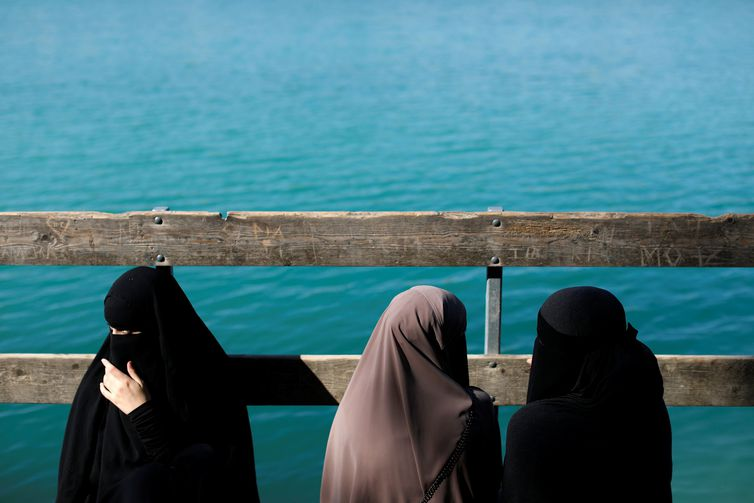 "Alaa (L), 21, Amina (C), 24, and Nayab, 18, sit on a dock during a visit to Karlstrup Kalkgrav, a lake near Karlstrup located outside Copenhagen, Denmark, July 19, 2018.  REUTERS/Andrew Kelly    SEARCH ""DENMARK VEIL"" FOR THIS STORY. SEARCH ""WIDER IMAGE"" FOR ALL STORIES. TPX IMAGES OF THE DAY. THE IMAGES SHOULD ONLY BE USED TOGETHER WITH THE STORY - NO STAND-ALONE USES"